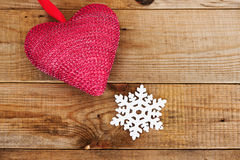Red heart and snowflake on wooden background. Royalty Free Stock Image