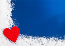 Red heart on snowy background Stock Photos