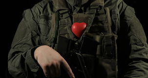 Red heart on the soldier`s chest, concept