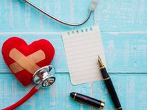 Red heart and stethoscope on blue bright wooden background. Heal stock image