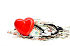 Red heart and stethoscope resting on pile of dollars Stock Image