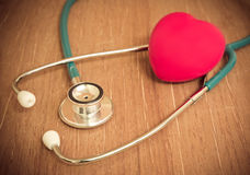 Red heart and stethoscope on wooden background Stock Photo