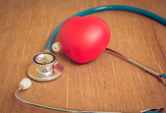 Red heart and stethoscope on wooden background Stock Photos