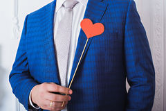 Red heart on a stick in a man's hands. Royalty Free Stock Image