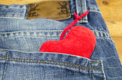 Red heart sticking out of a jeans back pocket Stock Photo