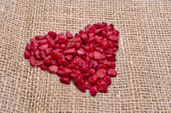 Red heart of stone. Red heart made of decorative stones on a hemp background stock photo