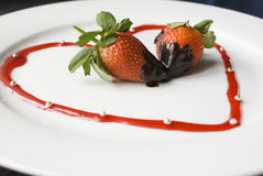 Red heart with strawberries. Red heart of juice with tasty strawberries in chocolat Royalty Free Stock Images