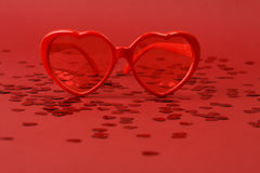 Red heart sunglasses on red background with red shining heart glitters Royalty Free Stock Images