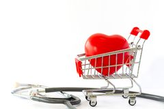 Red heart in a supermarket trolley and stethoscope. The concept of medicine and health insurance. Red heart in a supermarket trolley and stethoscope. The royalty free stock images