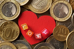 Red heart surrounded by various coins Royalty Free Stock Photo