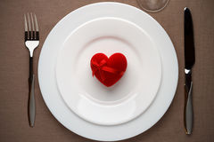 Red heart - a symbol of love on the white plate. Royalty Free Stock Images