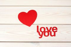Red  heart symbol on a wood background. Heart symbol cut out paper on a wood background with inscription  love you Stock Photos