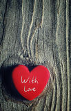 Red heart and the text `With love `. Red heart on a wooden old background. Romantic card Stock Images