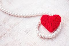 Red heart of thread and pearl beads on a wooden background. Glam. Orous elegant background for postcards and wedding invitations Royalty Free Stock Photo