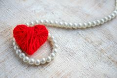 Red heart of thread and pearl beads on a wooden background. Glam. Orous elegant background for postcards and wedding invitations Stock Images