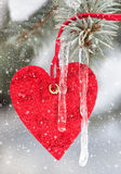 Red heart toy on fir tree with snowfall Royalty Free Stock Photography