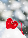 Red heart toy in snow on fir tree Royalty Free Stock Image