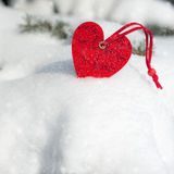 Red heart toy in snowfall on fir Royalty Free Stock Photography