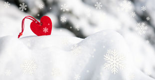 Red heart toy in snowfall on fir tree Stock Photos