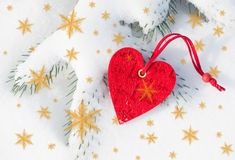 Red heart toy in snowfall on fir tree Stock Image