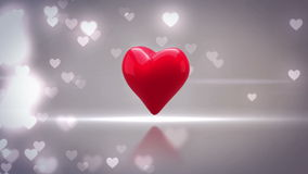 Red heart turning and exploding on glittering background stock footage