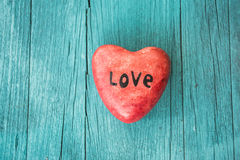 Red heart and turquoise wooden background in country style. Stock Photos