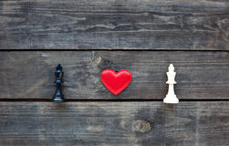 Red heart between two chess kings on rustic wood Royalty Free Stock Photo