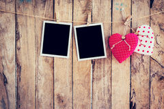 Red heart and two photo frame hanging on clothesline rope with w Stock Photo