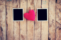 Red heart and two photo frame hanging on clothesline rope with w Stock Images