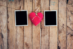 Red heart and two photo frame hanging on clothesline rope with w Stock Photography