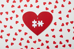Red heart with two white puzzle encircled with small hearts. Top view of red heart with two white puzzle encircled with small hearts. Love symbol. Valentine day Stock Image