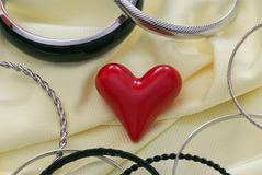Red heart with various bracelets Stock Photos