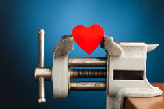 Red heart in the vice tool royalty free stock photos