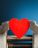 Red heart in the vice tool Royalty Free Stock Image