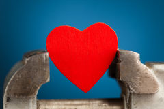 Red heart in the vice tool Stock Photo