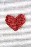 Red heart on white. Red heart put on white striped fabric Stock Photography