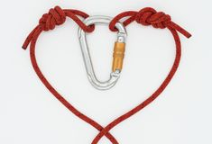 The rope is lined in the form of a heart. Red heart on a white background; Rope with knots united in symbol of love; Original congratulation for Valentine`s Day stock image