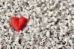 Red heart among white beads. Copy space. Stock Image
