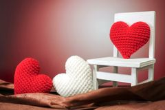 Red heart on white chair with brown background. Closeup Stock Image