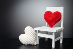 Red heart on white chair and white heart with black background -. Love concept Stock Image