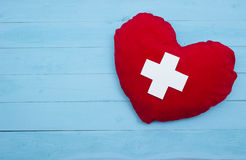 Red heart with a white cross on blue background Stock Photo