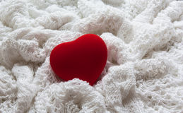 Red heart on a white knitted background. Valentine`s Day card. Red heart on a white background. The background is made of knitted fabric Royalty Free Stock Photos