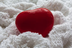 Red heart on a white knitted cloth. Valentine`s Day card. Red heart on a white background. The background is made of knitted fabric Stock Photos