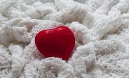 Red heart on a white knitted cloth. Valentine`s Day postcard. Red heart on a white background. The background is made of knitted fabric Royalty Free Stock Image