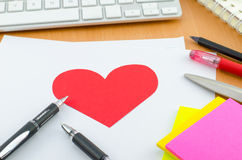 Red heart on white paper with pen on computer desk Stock Images