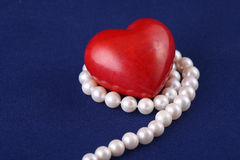Red heart on the white pearls Stock Photo