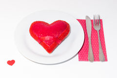 Red heart on white plate. Red heart on a white plate a fork and a knife on over a napkin Royalty Free Stock Images