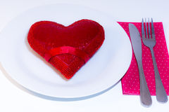 Red heart on white plate. Red heart on a white plate a fork and a knife on over a napkin Stock Photo