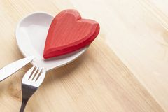 Red heart on a white plate in the form of a heart on a wooden background with a fork and knife. Festive background to the Valentine`s Day and Mother`s Day stock image