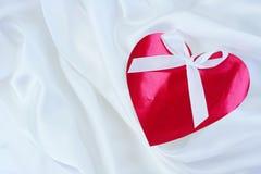 Red heart  on white satin Stock Photos